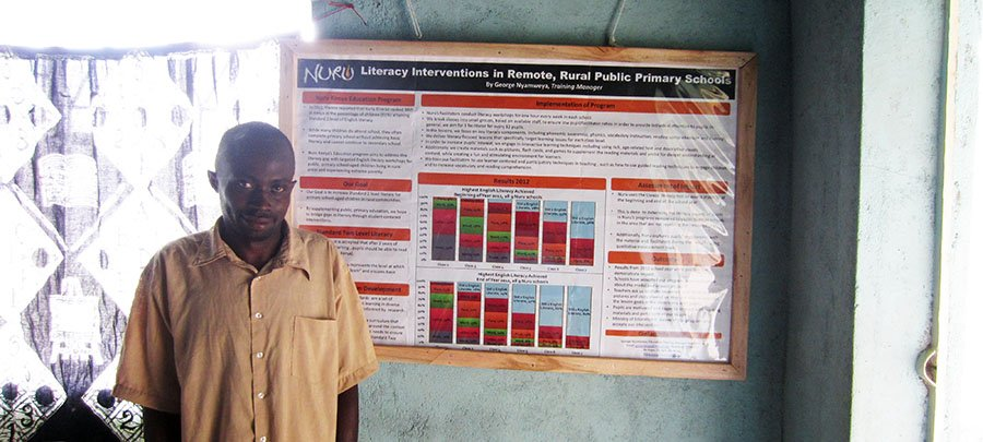 George Nyamweya standing beside the poster that he presented at the Pan-African Reading for All Conference on the Nuru Kenya Education Program