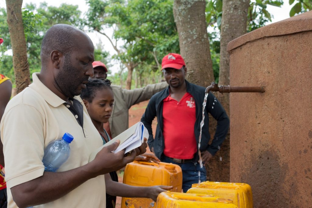 Birhanu Olle (WASH and Nutrition Field Officer) at a water source that needs repair.