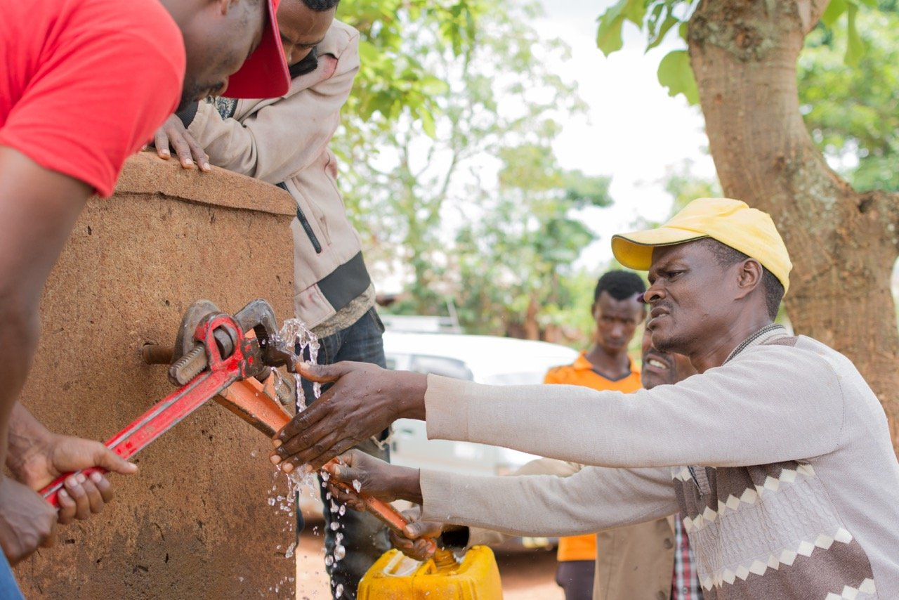 Water artisans and the Zonal Water and Mining Trainer working on repairing a water source in Dubana Bulo.