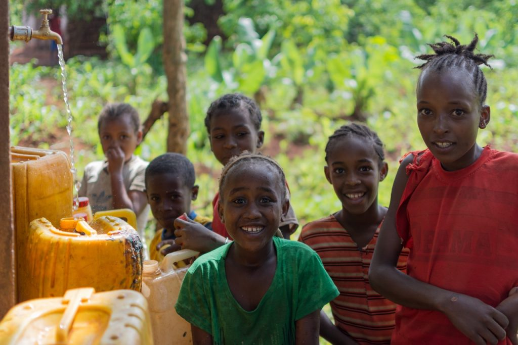 Children filling their jerry cans from a newly-repaired water source.