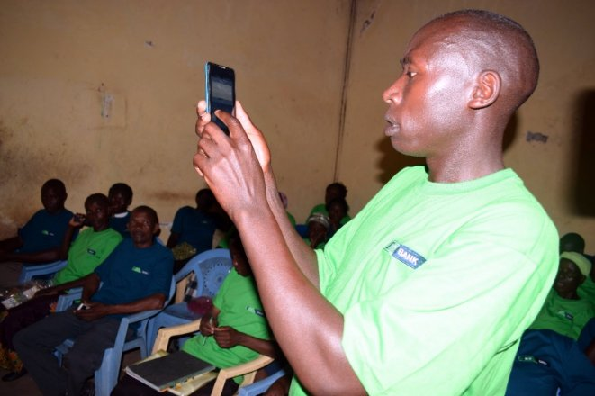 Nchama Samuel, a member of Kenya Group (one of the Chama Solutions Group) demonstrating to members how to borrow and approve loans through the KCB Chama Solution Digital Platform.