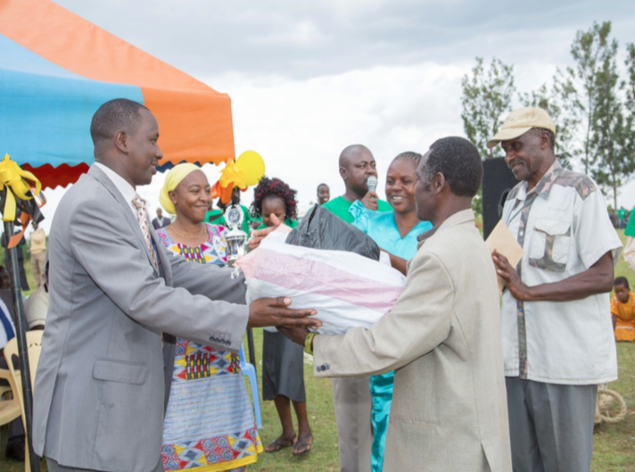 Rebwi Farmers Co-operative Chairperson (Rioba), Treasurer (Kohera) receiving an award from the Kuria East Sub-County Commissioner (Koech) during the International Day for the Eradication of Poverty (IDEP) on October 17th, 2016. Looking on is Nuru Kenya Country Director, Pauline Wambeti