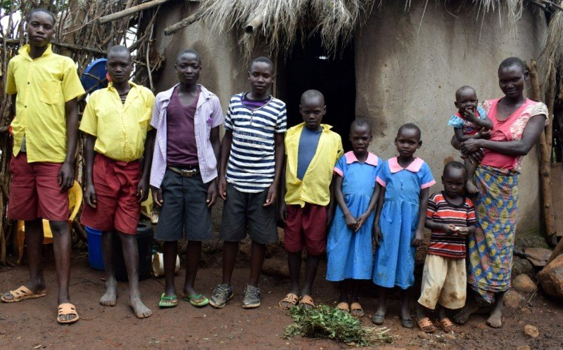 Lucy Mogesi Motabutwa together with her family outside her hut in Ikerege village, Migori County - Kenya